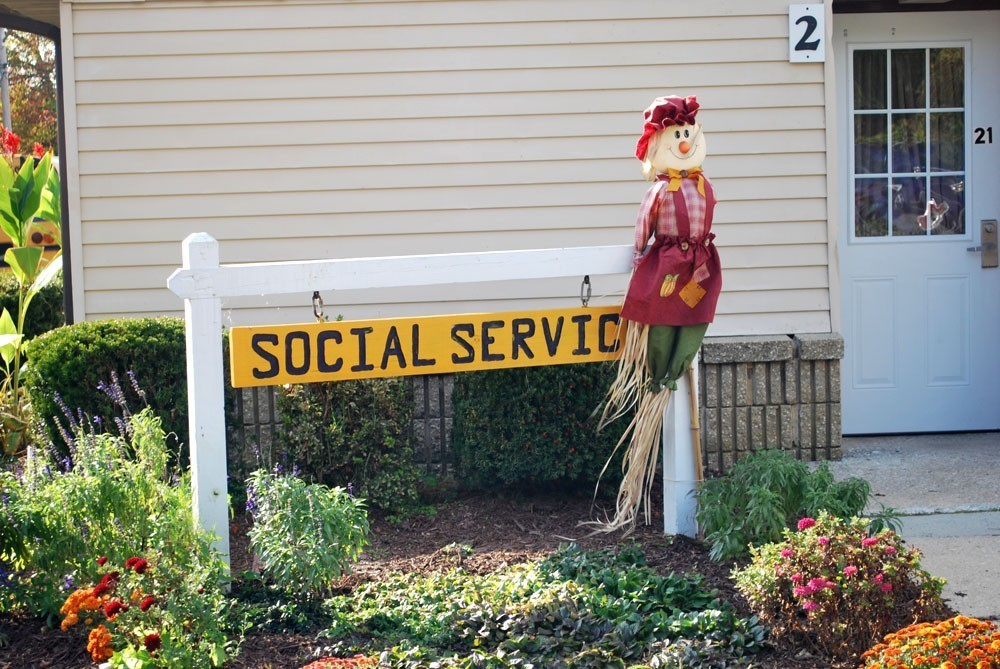 Social Services sign with fall scarecrow