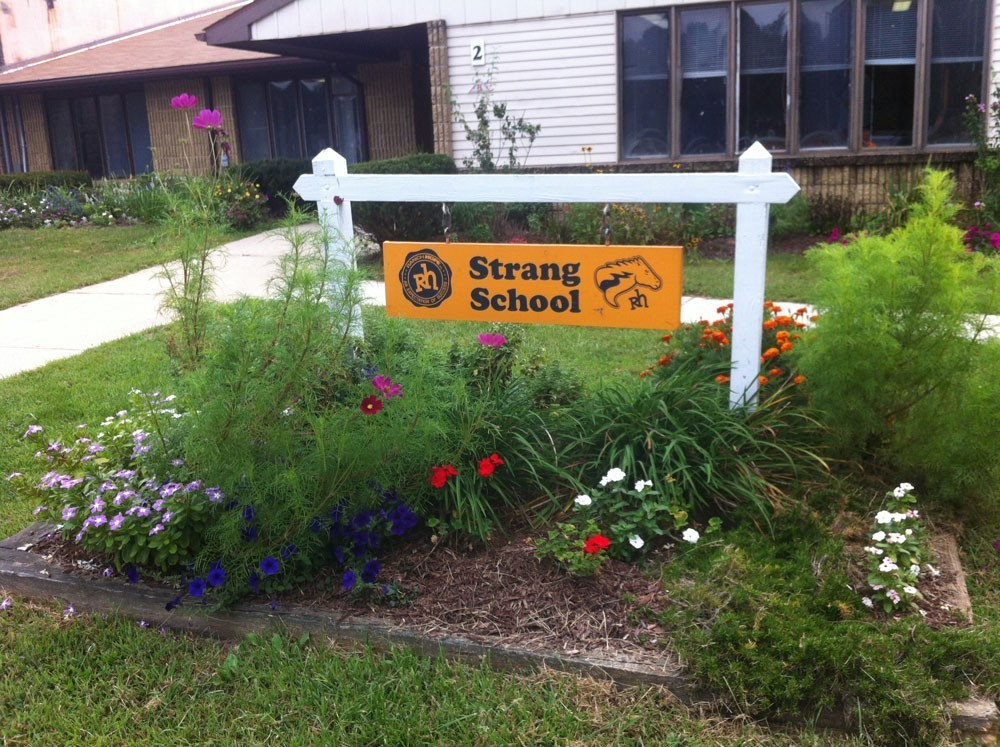 Strang School sign with flowers planted around it
