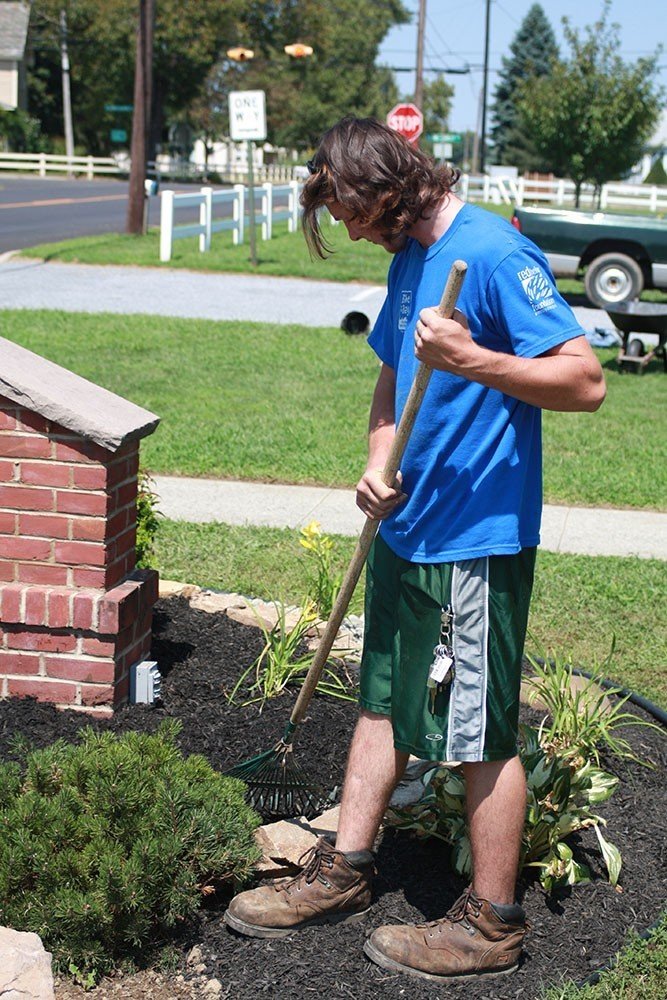 Young man working in flower bed