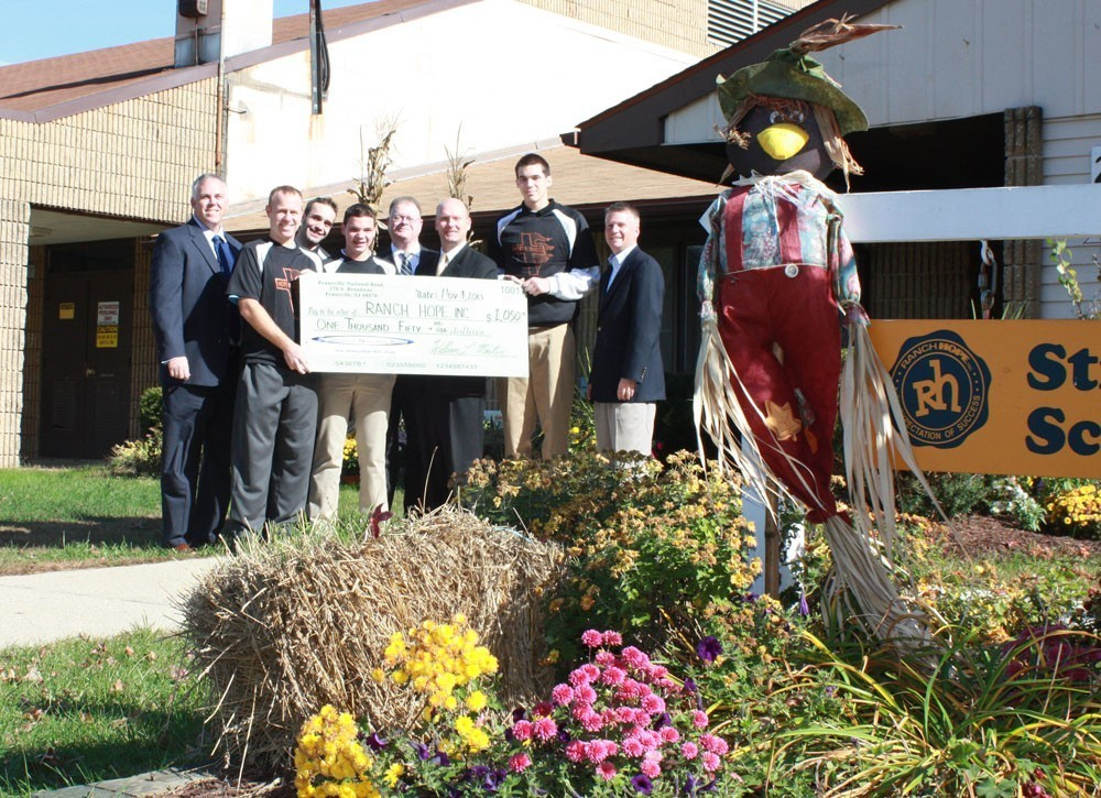Group posing outdoors with large check behind flower bed