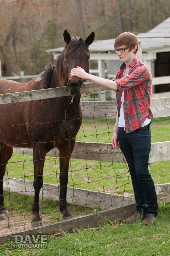 Young man petting a horse
