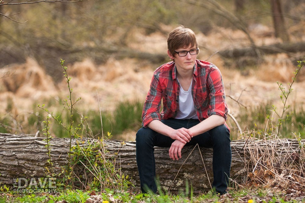Young man sitting on log